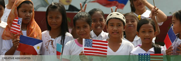 Boys and girls waving U.S. and Philippine flags