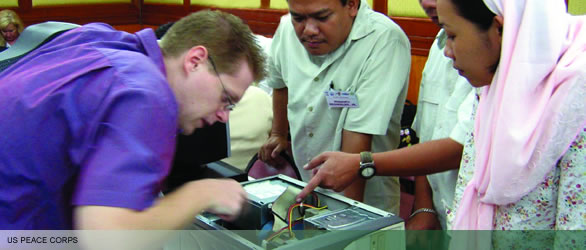 Peace Corps volunteer and three Filipinos examining the inside of a computer